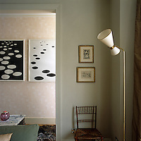 A brass floor lamp with an unusually shaped lampshade stands in the corner of this living room  and the doorway frames a pair of lithographs by Alexander Calder
