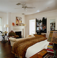 The white master bedroom features a Victorian armchair, leopard print throw, a painting by Julia Jacquette and a photograph by Spencer Tunick