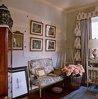 Old documents and gilt-framed prints line the walls of this feminine blue and white sitting room