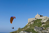 St Ives, Cornwall, England. Paraglider by the sea below a stone chapel.