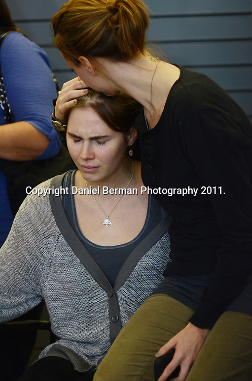 Amanda Knox is comforted by her sister, Deanna Knox, right, after speaking to the media at a press conference upon her arrival in the United States at Seattle-Tacoma International Airport in Seattle Tuesday, October 4. Knox's murder conviction was overturned by an Italian appellate court after spending four years in prison in Italy. Photo by Daniel Berman/www.bermanphotos.com.