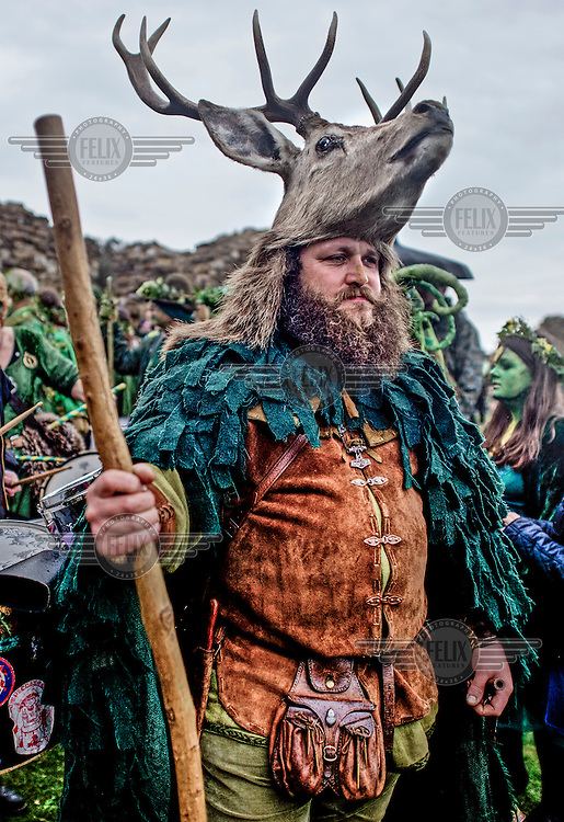 A man wearing a dear head hat at a Jack in the Green festival. The festival is part of a recent revival of an older custom where people would wear frameworks covering much of their bodies which were decked out in foliage. The custom is connected to English May Day parades that herald  the coming of summer.