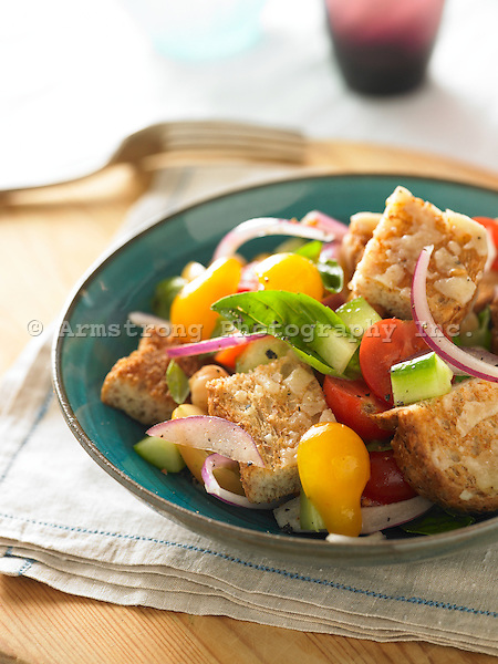 Panzanella (bread salad) with whole wheat bread, cherry tomatoes, cucumbers, chickpeas, red onion, fresh basil leaves.