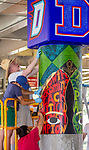 "Brother Mark Elder, C.M., an adjunct faculty member in DePaul's art, media and design program, works with a group of current and former students, Saturday, July 28, 2018, as they install the second of three new murals under the Fullerton ""L"" Station in Lincoln Park. The colorful montage of historical images highlighting the 50th anniversary of DePaul's Black Student Union also remembers the student protests of 1969 held on campus. Other recent installations included a caricature of DePaul basketball star George Mikan, a 1959 Naismith Memorial Basketball Hall of Fame inductee, and a mural celebrating the opening of DePaul's Loop Campus.<br /> <br /> Elder's artistic retrospective, titled ""The Story of 'The Little School Under the 'L'', will eventually feature 25 murals permanently installed on the massive concrete pillars that support the ""L"" station nearest the university's Lincoln Park Campus. (DePaul University/Jamie Moncrief)"