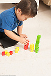 Three year old boy building towers of colored wooden cubes sorting them by color