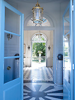 A 19th century Louis XVI style lantern and inlaid marble flooring in the entrance hall; the doors are painted in a custom colour based on an 18th century hue