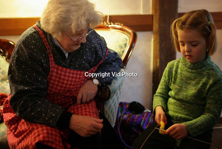 ARNHEM - Kinderen krijgen tijdens de winteropenstelling tot 14 januari in het Nederlands Openluchtmuseum in Arnhem breiles. Vorig jaar was de 'spoedcursus' een enorm succes en ook dit jaar is de belangstelling enorm. Volgens de breileraressen heeft dat alles te maken met de hernieuwde belangstelling in ons land voor ouderwetse handwerkactiviteiten en nostalgie. Foto: VidiPhoto
