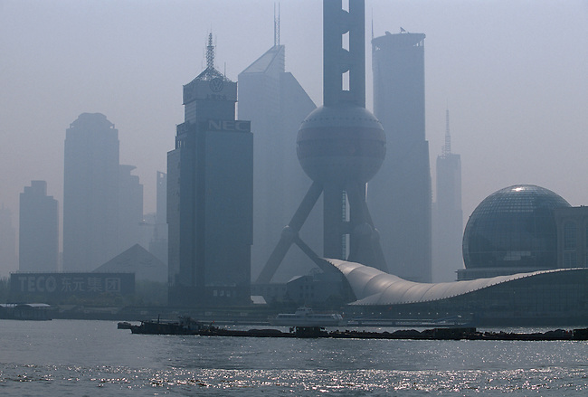 Barges on the Huangpu River crossing in front of the Pudong New Area on a hazy morning in Shanghai China