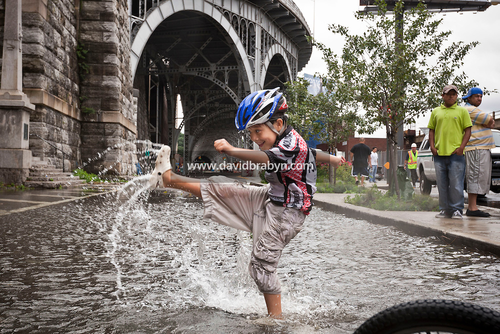 6 year-old Crois Galvan-Dubois plays in a rain water flooded section of 12th Avenue in Hamilton Heights, New York City, NY, USA shortly after tropical storm Irene passed over the city, 28 August 2011.