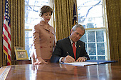 """Washington,D.C. - December, 19, 2006 -- First lady Laura Bush stands by United States President George W. Bush as he signs S. 843, the """"Combating Autism Act of 2006,"""" which authorizes appropriations through FY 2011 for Autism Spectrum Disorder research, screening, intervention, and education, in the Oval Office Tuesday, December 19, 2006. .Credit: Eric Draper-White House via CNP"""