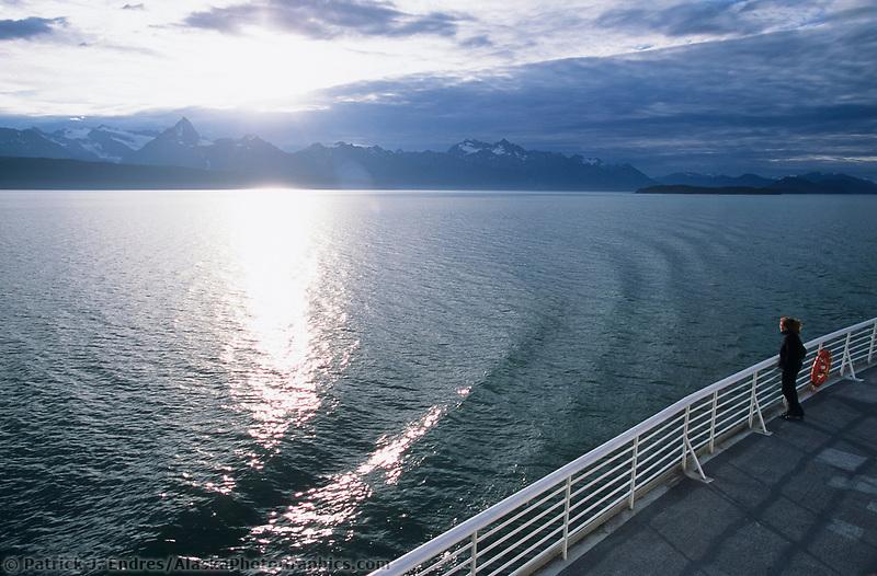 Tourist stands on the deck of the Alaska marine ferry, Juneau, Alaska