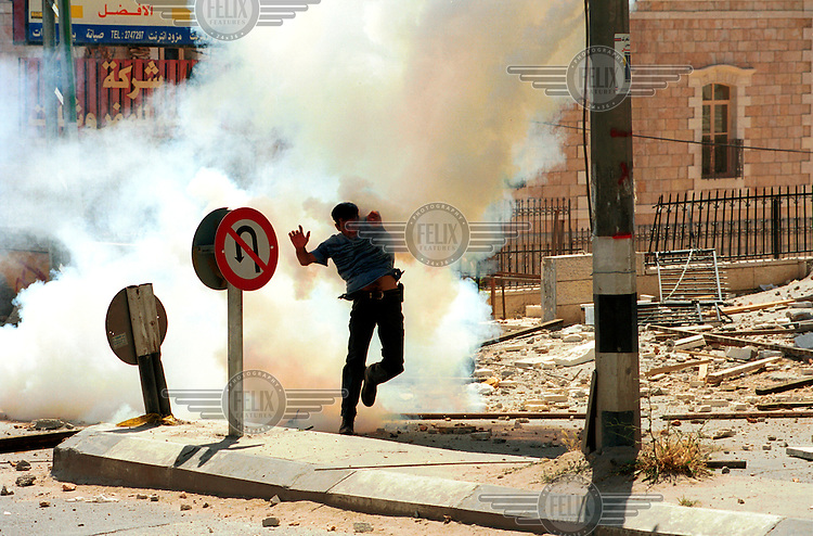 """A Palestinian man tries to avoid a tear gas grenade during """"Naqba Day"""" clashes in the West Bank city of Bethlehem.  The annual """"Naqba Day"""" is observed by Palestinians and Arab-Israelis, to commemorate the 'Palestinian holocaust' than accompanied the birth of Israel in 1948."""