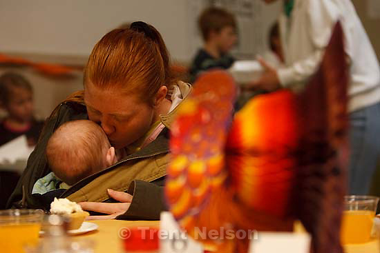 Salt Lake City - Melissa Wilson of West Jordan kisses her 5-month old daughter Kalya McBride at an early Thanksgiving. A large number of homeless and low-income individuals were served an early Thanksgiving feast at the Rescue Mission Tuesday November 25, 2008. In addition to a turkey dinner with apple, pecan, cherry and pumpkin pie, there were free flu shots, free haircuts and free backpacks. Tuesday November 25, 2008.
