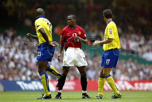 August 10, 2003: ERIC DJEMBA-DJEMBA is kicked in the leg by Sol Campbell off the ball, Arsenal 1 v MANCHESTER UNITED 1 (Man Utd won 4-3 after penalties), The FA Community Shield 2003, The Millennium Stadium, Cardiff. Photo: Neil Tingle/Action Plus...030810.Association Football Soccer.Footballer footballers player players.premiership premier league.violent conduct unsporting