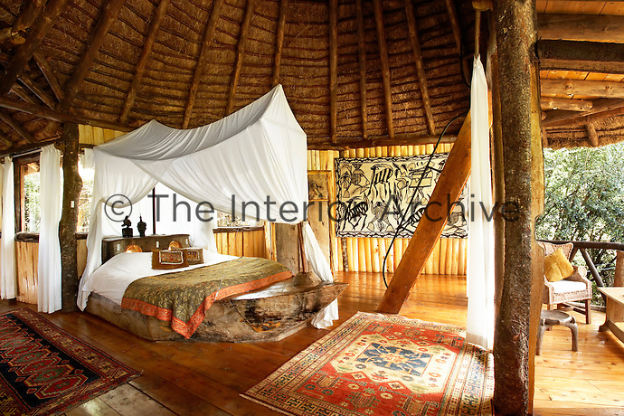 The bedroom of a boutique style luxurious wooden treehouse, made entirely of wood and grass. The interior has a rustic feel, with the talents of regional artists adding many of the finishing touches, for example a Swahili canoe forms the base of the bed in Boat Room and the graphic tribal batik is from Ivory Coast. Antique kilims are laid on the floor.