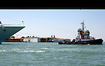 Tug guiding ship into harbour, Venice lagoon, Italy.