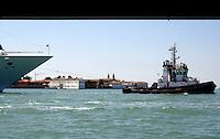 Tug guiding ship into harbour, Venice lagoon, Italy.