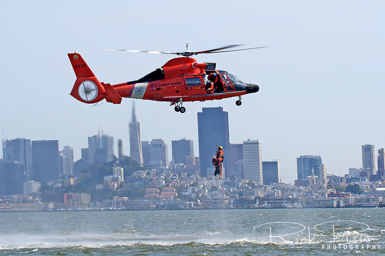 A Coast Guard swimmer is raised to a HH-65C Dolphin helicopter. The helicopter and crew, based at U.S. Coast Guard Air Station San Francisco, was on a practice mission with the Coast Guard Auxilary to maintain search and rescue proficiency.