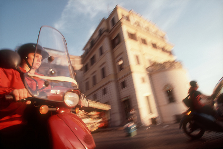 Rome, Italy, Motorini, Italian woman on motor scooter at speed near the Spanish Steps at sunset.