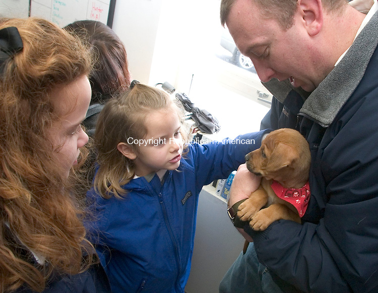 MIDDLEBURY, CT - 21 JANUARY 2007 - 012107JW07.jpg -- Julia Dingee age 8 and her sister Meg Dingee age 5 exchange curious looks with a Mastif-Pit puppy held by their father Todd Dingee of Middlebury during the Middlebury Animals for Life shelter pet adoption Sunday afternoon. The Dingees have statrted the process of adopting a pet and hope to have one soon. Jonathan Wilcox Republican-American