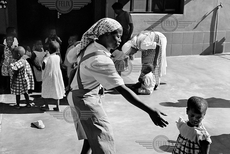 A nun reaches out to an orphan child in an orphanage in Maputo, Mozambique on February 21, 2001. More than 13 million African children have been orphaned by the AIDS pandemic. Worldwide, more than 20 million people have died since 1981.