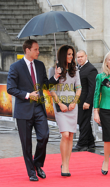 Prince William, Duke of Cambridge and Catherine, Duchess of Cambridge.'African Cats' UK Premiere at BFI Southbank, London, England..25th April 2012.full length kate royals royalty married husband wife blue suit grey gray dress turquoise gold beads beaded umbrella profile clutch bag.CAP/WIZ.© Wizard/Capital Pictures.