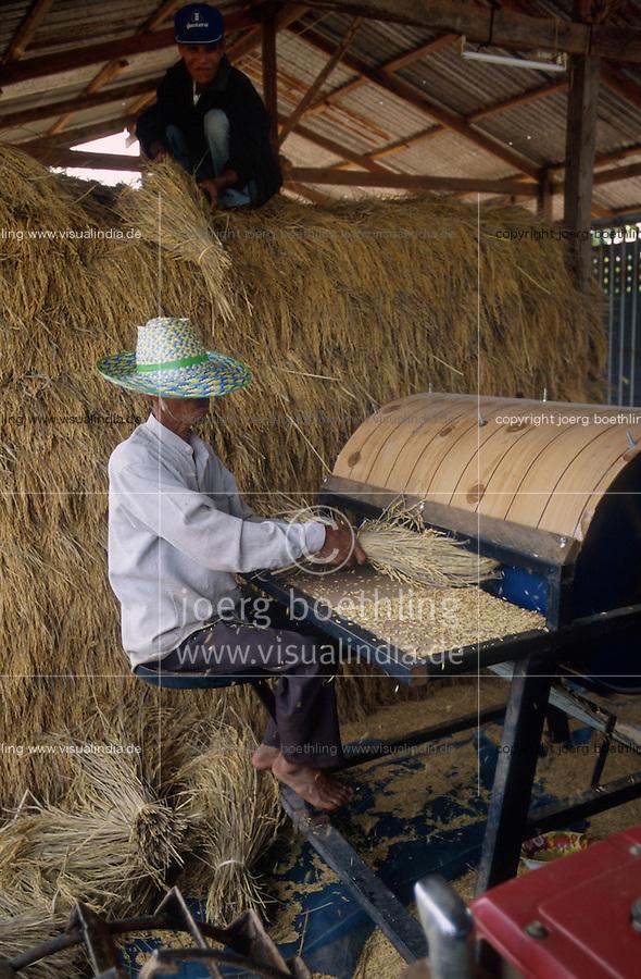 THAILAND, Ubon Ratchathani, fair trade and organic farmer project, PFA Progressive Farmer Association, threshing with machine after harvest of organic Jasmine fragrant rice / THAILAND, fairtrade und Bio Projekt, PFA Progressive Farmer Association, Dreschen mit Maschinenach Ernte von Jasmin Duftreis
