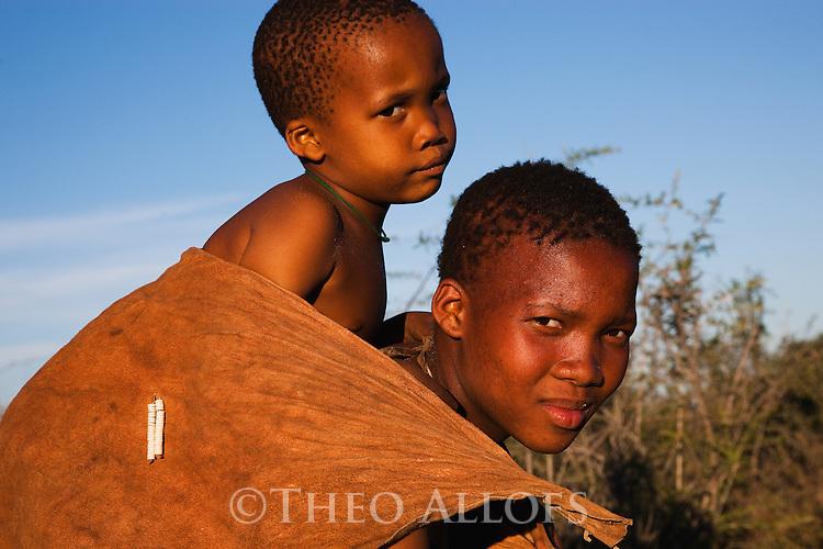 Botswana, Kalahari, bushman (san) mother carrying young child on her back
