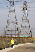 Security guard and electricity pylons at the Olympic Park site in Stratford.