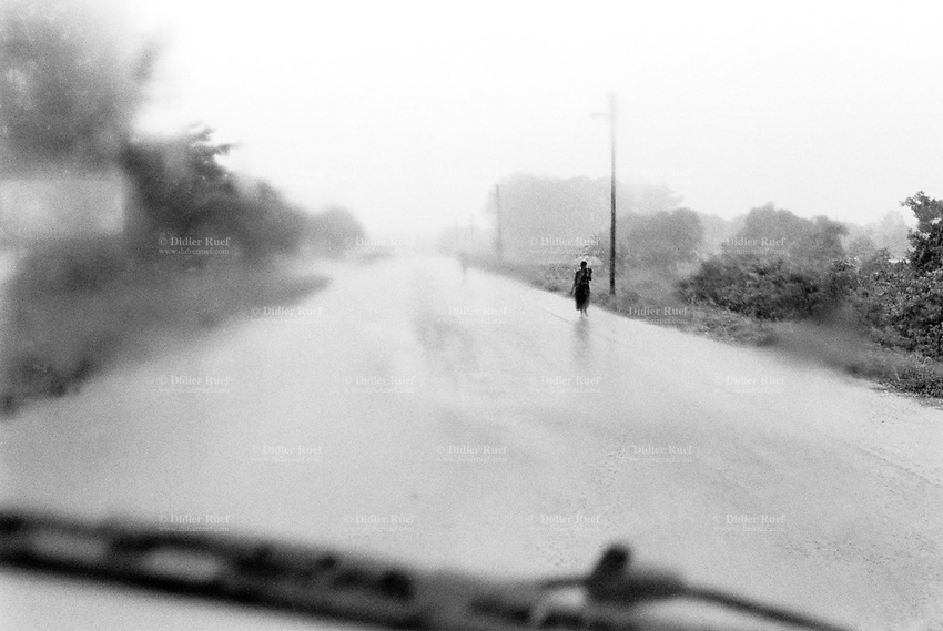 Mozambique. Province of Gaza. Macia. A woman walks with her umbrella on the road under the rain. © 2000 Didier Ruef