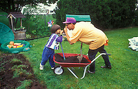 Little boy and dad holding their noses over a wheelbarrow of manure for backyard gardening