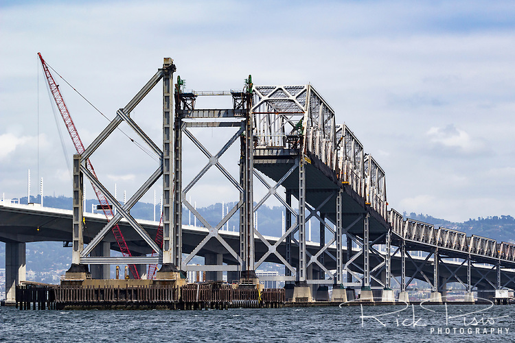 With its replacement in the background, and in use, the eastern span of the San Francisco Bay Bridge is slowly disassembled and removed from San Francisco Bay. The section removed dates back to the 1930's and once carried traffic for US 40, US 50, and Interstate 80.