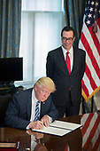 US President Donald J. Trump (L), with Secretary of Treasury Steven Mnuchin (R), signs a financial services Executive Order during a ceremony in the US Treasury Department building in Washington, DC, USA, 21 April 2017. President Trump is making his first visit to the Treasury Department for a memorandum signing ceremony with Secretary Mnuchin.<br /> Credit: Shawn Thew / Pool via CNP