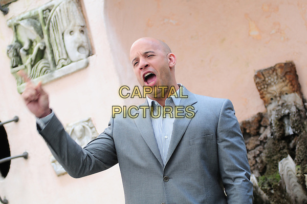 "VIN DIESEL (Mark Sinclair Vincent).Photocall for ""Fast & Furious"", Rome, Italy..March 25th, 2009.half length suit jacket hand arm fist mouth open funny face grey gray .CAP/CAV.©Luca Cavallari/Capital Pictures."