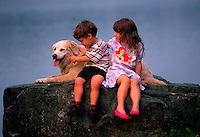 A young girl and boy sit with their Golden Retriever dog on a rock near water.