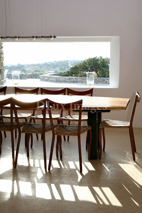 wooden dining room...Savina Giakos and her husband created a minimal and practical cottage.house on the island of Paros in Greece....