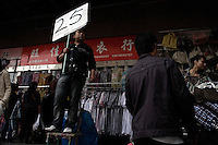 Crowds walk past sellers at a fake designer goods market in central Shanghai, China.