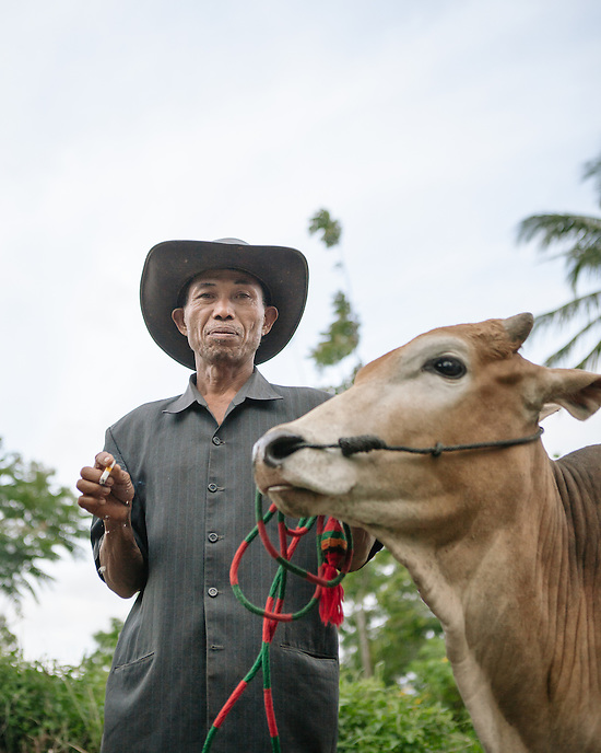 A bull's owner posing for a portrait.