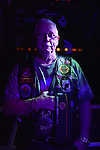 Freeport, New York, USA. September 10, 2014. FRANK NEAL, of Hempstead, an American Legion Riders Post #1488 member, holds his hand over his heart while 'Gold Bless America' is sung, at night on board the boat Miss Freeport V, which sailed from the Woodcleft Canal of the Freeport Nautical Mile after a dockside remembrance ceremony in honor of victims of the terrorist attacks of September 11 2001. American Legion, Patriot Guard Riders, and Captain Frank Rizzo hosted the ceremonies on the eve of the 13th anniversary of the 9/11 attacks.