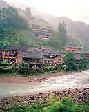 CHINA, Longsheng, stream in front of houses with mountain in the background in the village of Longsheng