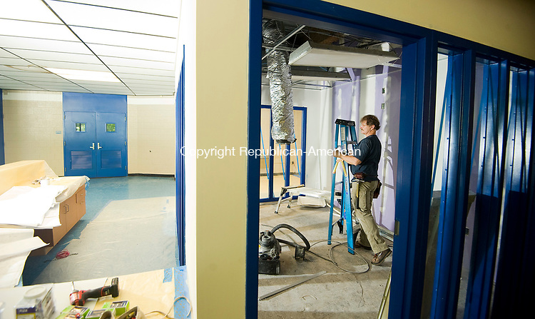 WATERBURY, CT-080917JS01-- Dane Lilly, and electrician with John L Simpson & Co Inc, of Bridgeport,  works on lighting inside one of the new offices as construction continues Wednesday at Crosby High School in Waterbury. Jim Shannon Republican-American