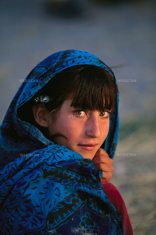 Portrait of a little Afghan girl. <br /> The Pashtun Tribal Zone has been a crossroads and a territory occupied by waves of armed forces over the course of the fifth phase of the Afghan war (2001&ndash;2014). It links Pakistan with Afghanistan and was a gathering place for nomadic populations. The Federally Administered Tribal Areas of Pakistan, linked with Pakistan&rsquo;s northwest provinces, is mostly peopled with Pashtun tribes who are sometimes hostile to the Pakistan government. A lawless zone which has seen little development, this region is a source of tension between Pakistan and Afghanistan. Since 2004, it has been the epicenter of violent conflicts of the northwest territories between the army of Pakistan and several Islamist groups. This is an area of massive strategic and geopolitical importance. This photo was shot over the course of a reportage on the tribal zones entitled &ldquo;On Bin Laden&rsquo;s Trail&rdquo; for National Geographic Magazine.<br /> Afghanistan, zone tribale pachtoune, 2004 Portrait d&rsquo;une fillette afghane.  <br />