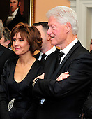 Former United States President Bill Clinton, right, speaks with Capricia Penavic Marshall, Chief of Protocol of the United States, left, as he watches the recipients of the 2011 Kennedy Center Honors pose for a photo following a dinner hosted by United States Secretary of State Hillary Rodham Clinton at the U.S. Department of State in Washington, D.C. on Saturday, December 3, 2011. The 2011 honorees are actress Meryl Streep, singer Neil Diamond, actress Barbara Cook, musician Yo-Yo Ma, and musician Sonny Rollins..Credit: Ron Sachs / CNP