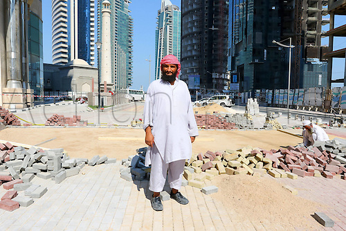 22.01.2015, Doha Qatar. FIFA World Cup 2022 preparations as a worker stands in front of partially completed high-rise buildings and streets in very hot and humid conditions
