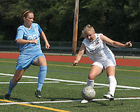 Boston Aztec forward Corey Persson (17) crosses the ball as Seacoast United Mariners midfielder Annie Koensgen (24) closes. In a Women's Premier Soccer League (WPSL) match, Boston Aztec (white) defeated Seacoast United Mariners (blue), 2-1, at North Reading High School Stadium on Arthur J. Kenney Athletic Field on on June 23, 2013. Due to injuries through the season, Seacoast United Mariners could only field 10 players.