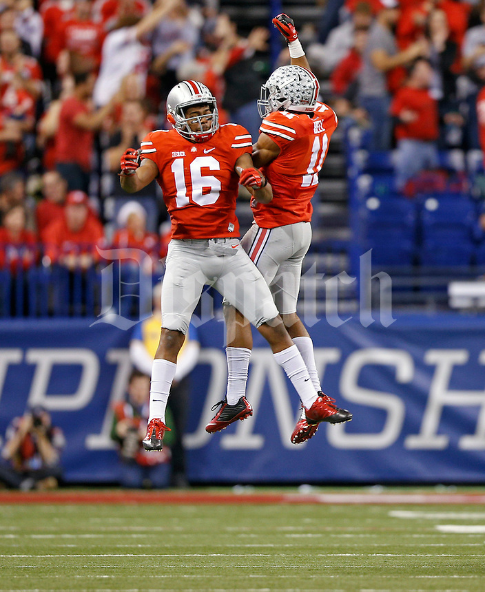 Ohio State Buckeyes defensive back Vonn Bell (11) celebrates his interception with Ohio State Buckeyes defensive back Cam Burrows (16) against Wisconsin Badgers during the 1st quarter in the 2014 Big Ten Football Championship Game at Lucas Oil Stadium in Indianapolis, Ind. on December 6, 2014.  (Dispatch photo by Kyle Robertson)