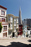 USA, California, San Francisco, a woman reads and people walk up the steep Kearny street, the Transamerica Pyramid in the distance, North Beach