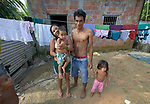 A family poses in front of their house in the Nacoes Indigenas neighborhood in Manaus, Brazil. The neighborhood is home to members of more than a dozen indigenous groups, many of whose members have migrated to the city in recent years from their homes in the Amazon forest.