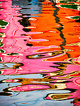 Colorful reflections in the dancing waters of the canals in the colorful village of Burano, Italy.