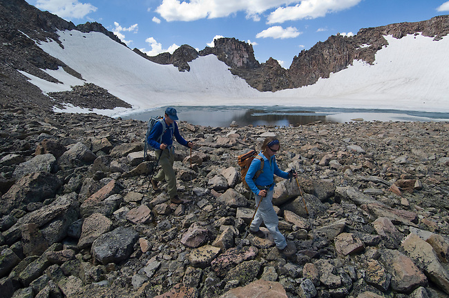 couple, (MR), hiking, hike, recreation, outdoors, back country, Rowe Glacier, lake, rock scree, talus piles, high elevation, alpine, landscape, cumulus, clouds, rocky, snow, summer, August, afternoon, Rocky Mountain National Park, Colorado, USA